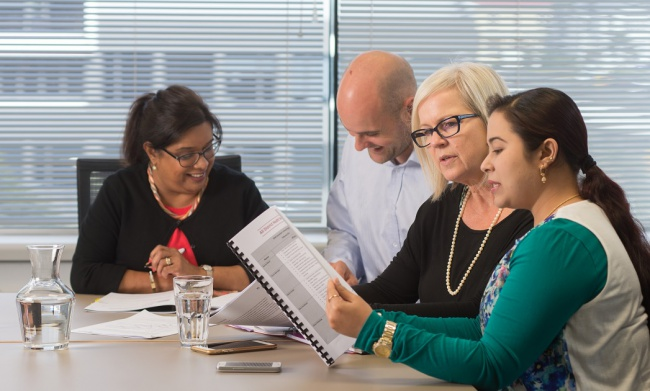 Four people in a meeting read and discuss Workforce Information and Projects.
